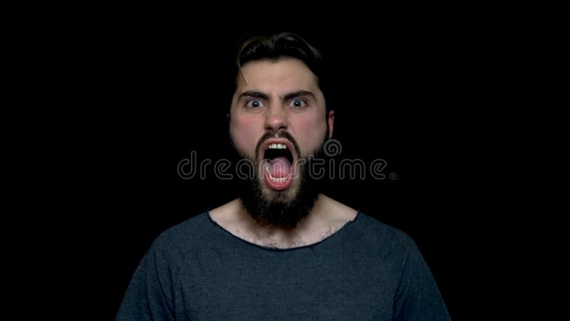 Portret van de gebrul knappe mens met baard die en zich met grote open die mond bevinden gillen, op zwarte achtergrond wordt geïs royalty-vrije stock foto