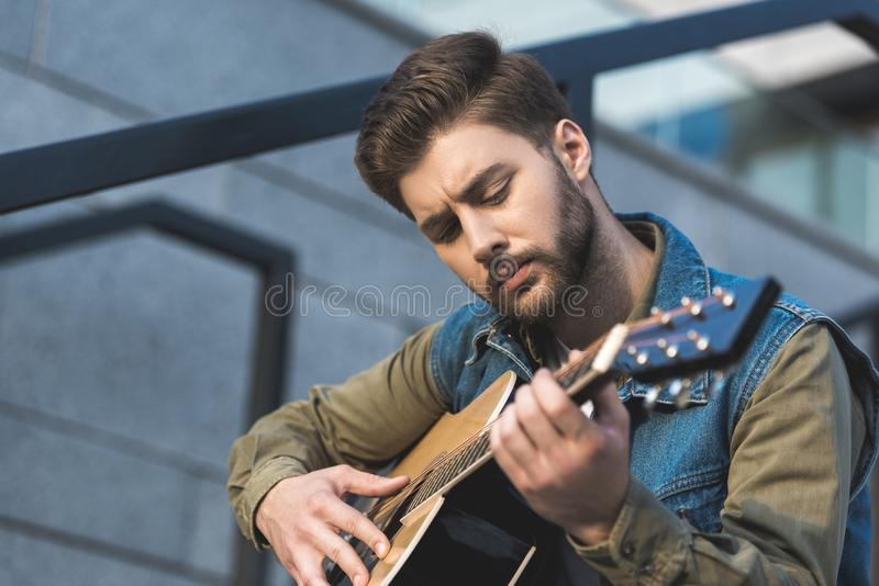 portret van de geconcentreerde mens die akoestische gitaar spelen stock afbeelding