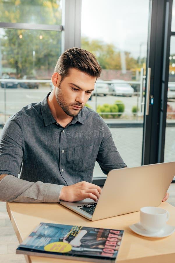 portret van de geconcentreerde mens die laptop met behulp van terwijl het zitten bij lijst stock afbeelding