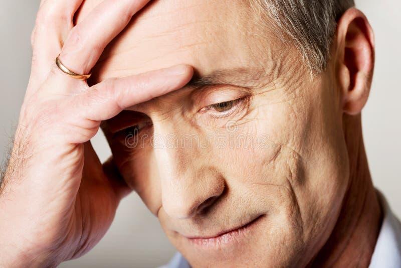Portret van de gedeprimeerde rijpe mens wat betreft zijn hoofd royalty-vrije stock afbeelding