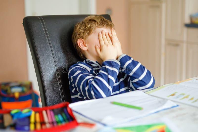 Portret van de gefrustreerde schreeuwende droevige jongen die van het schooljonge geitje thuis thuiswerk maken Weinig kind die me stock afbeeldingen