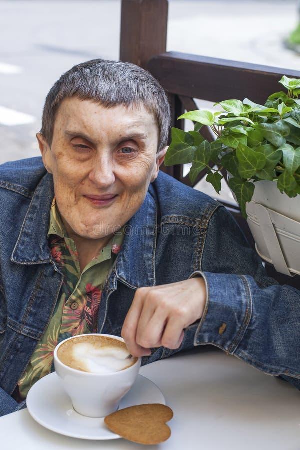 Portret van de gehandicapte mens met hersenverlammingszitting bij koffie en het drinken koffie stock fotografie