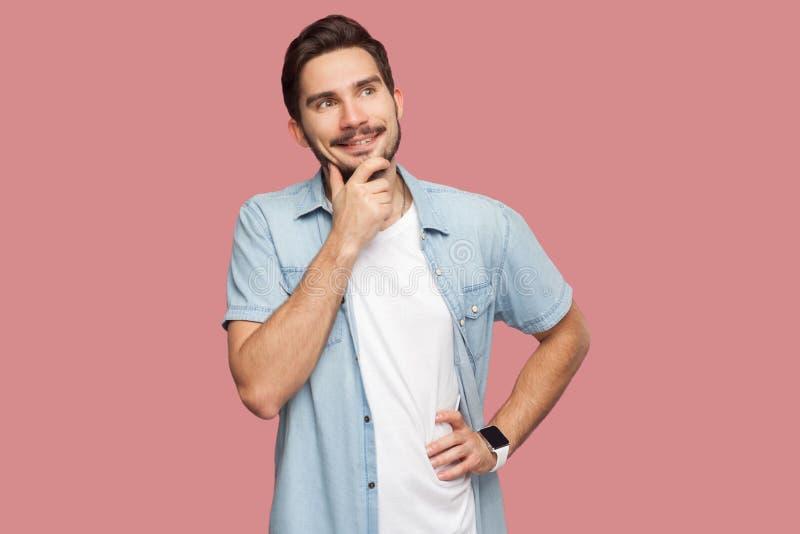 Portret van de gelukkige dromerige knappe gebaarde jonge mens in blauw toevallig stijloverhemd die bevinden, zich wat betreft zij stock afbeeldingen