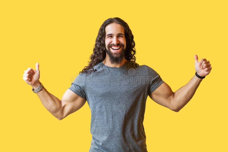 Portret van de gelukkige gebaarde jonge mens met lang krullend haar in grijze t-shirt die zich met duimen bevinden omhoog en came royalty-vrije stock foto's