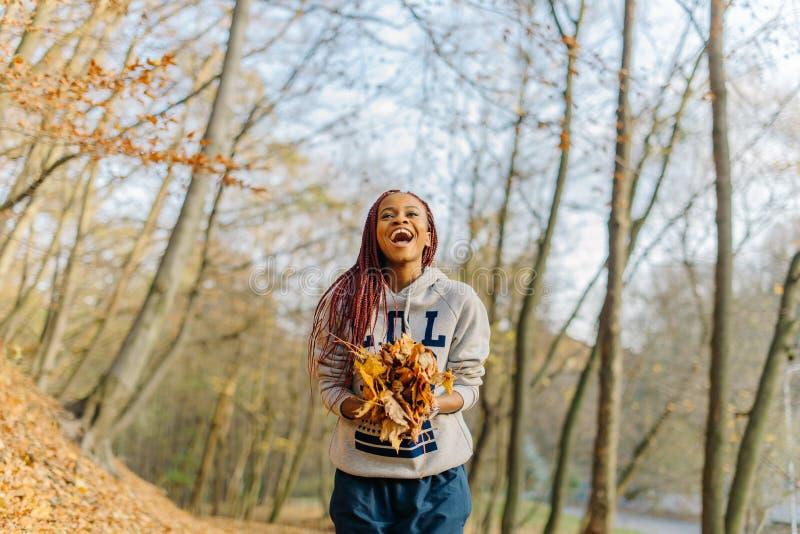 Portret van de gelukkige glimlachende Afrikaanse vrouw die in sportkleding de bos van vergeelde bladeren in de herfstpark houden royalty-vrije stock fotografie