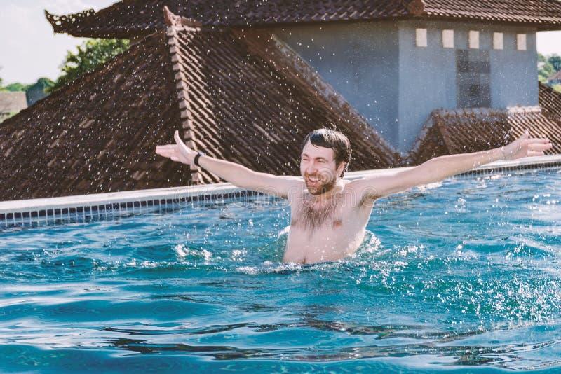Portret van de gelukkige glimlachende jonge mens met omhoog handen, dat in pool op dak wordt gebaad royalty-vrije stock fotografie