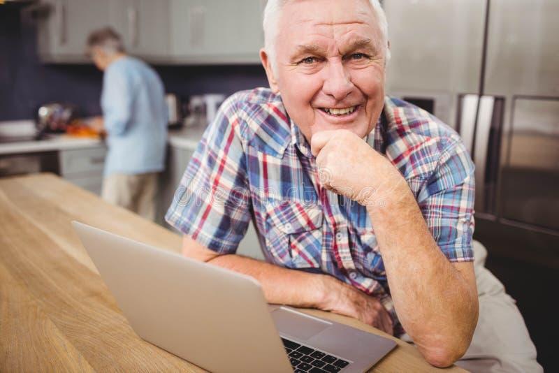 Portret van de gelukkige hogere mens die laptop en vrouwen het werken in keuken gebruiken stock fotografie