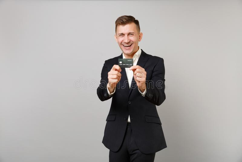 Portret van de gelukkige jonge bedrijfsmens in klassiek zwart die kostuum, het kredietbetaalpas van de overhemdsholding op grijze stock foto