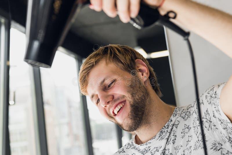 Portret van de gelukkige kam van de kapperholding en slagdroger in salon stock fotografie