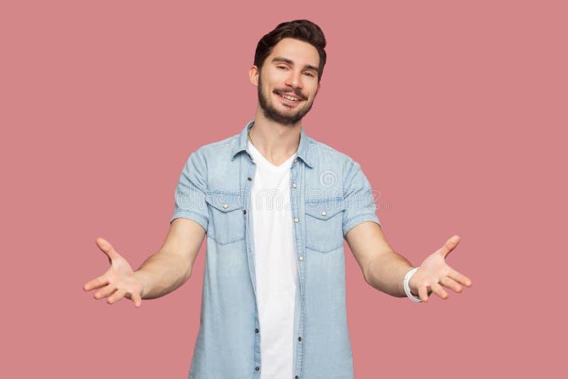 Portret van de gelukkige knappe gebaarde jonge mens in blauw toevallig stijloverhemd die zich met opgeheven wapens bevinden en ca stock foto