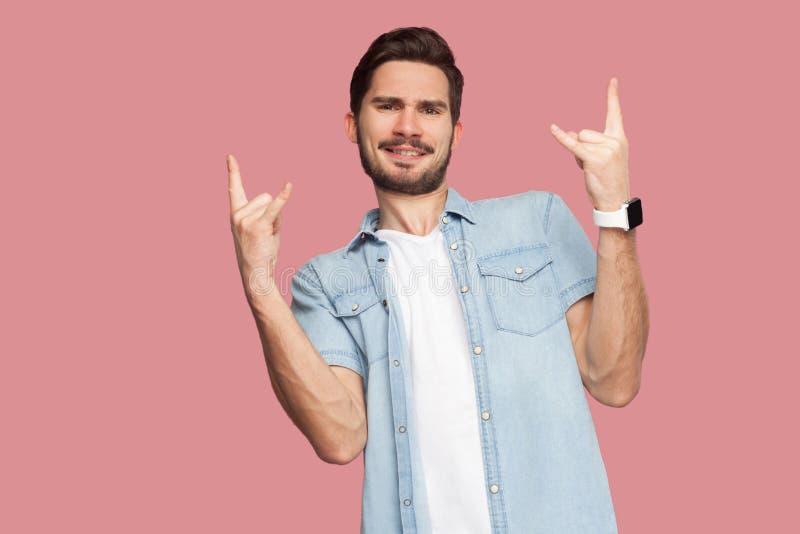 Portret van de gelukkige knappe gebaarde jonge mens in blauw toevallig stijloverhemd die zich met rotsteken bevinden en camera me stock foto