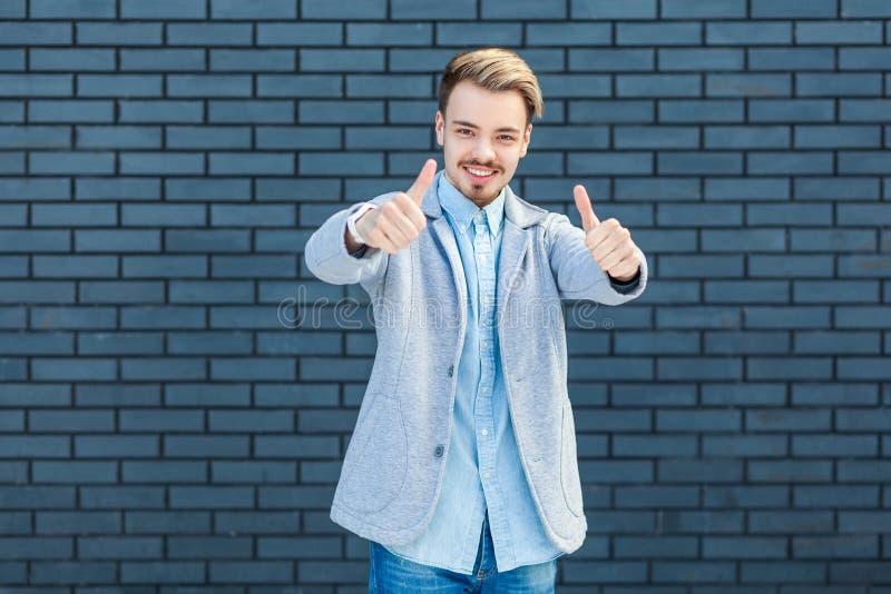 Portret van de gelukkige knappe jonge blondemens in toevallige stijl die zich met omhoog duimen, zoals gebaar bevinden, en het be royalty-vrije stock afbeeldingen