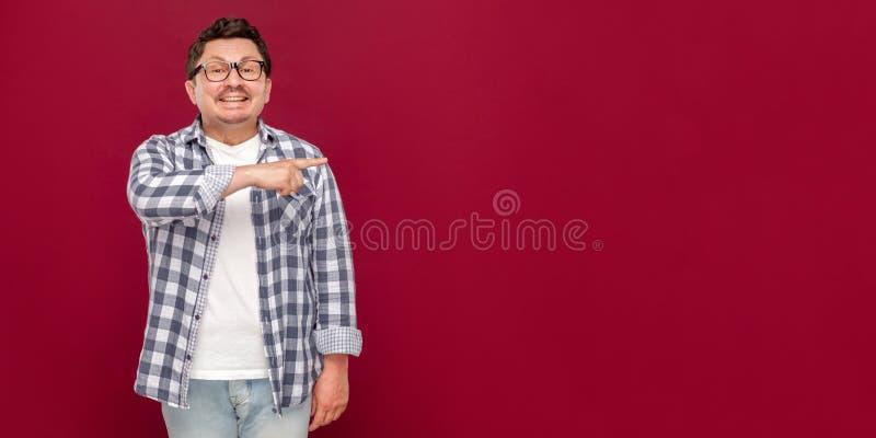 Portret van de gelukkige knappe midden oude bedrijfsmens in toevallig geruit overhemd en oogglazen die en zich op copyspace bevin royalty-vrije stock afbeelding