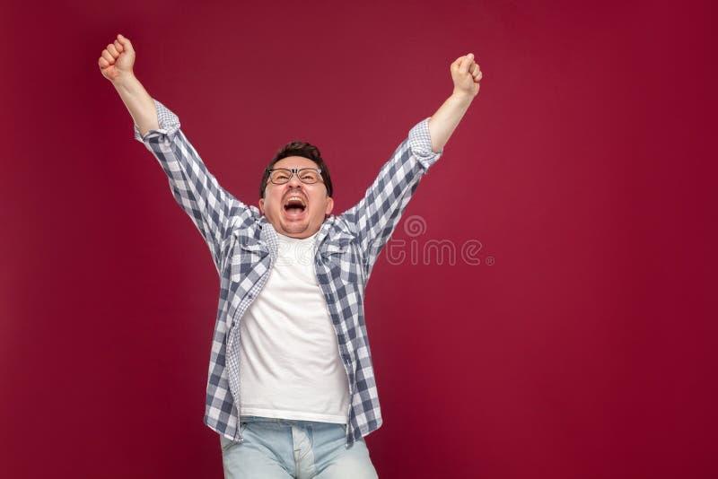Portret van de gelukkige knappe midden oude mens in toevallig geruit overhemd, oogglazen die holdingshanden opstaan die, gillen e stock foto's
