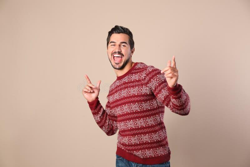 Portret van de gelukkige mens in Kerstmissweater op beige stock fotografie