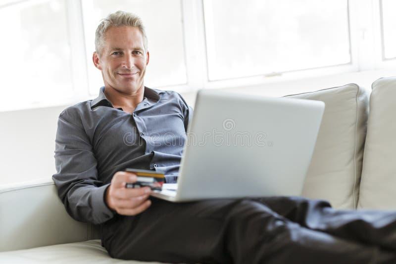 Portret van de gelukkige rijpe mens die laptop met behulp van die op bank binnenshuis liggen stock foto's