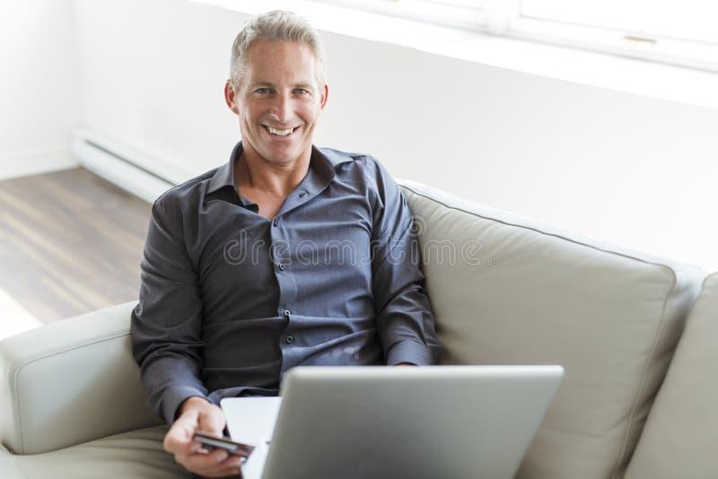 Portret van de gelukkige rijpe mens die laptop met behulp van die op bank binnenshuis liggen royalty-vrije stock afbeeldingen