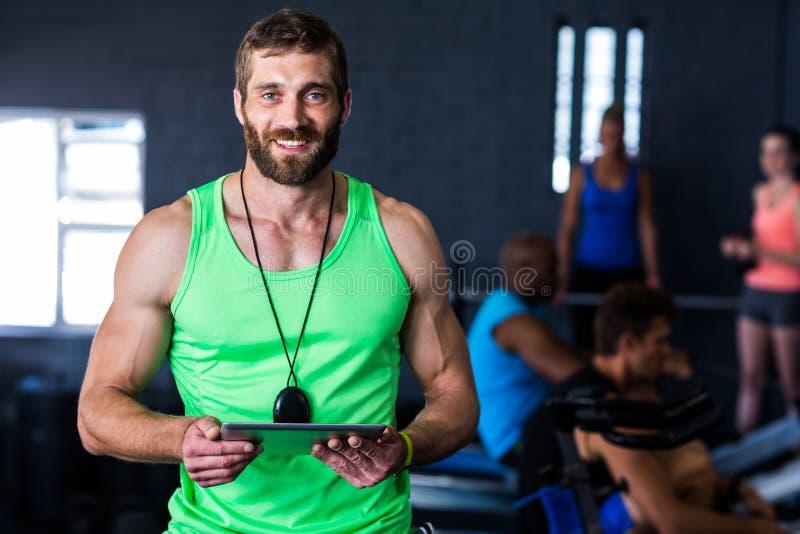 Portret van de gelukkige tablet van de hipsterholding in gymnastiek stock fotografie