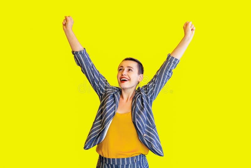 Portret van de gelukkige verraste mooie vrouw van het winnaar jonge korte haar in geel overhemd en toevallig stijl gestreept kost stock foto's