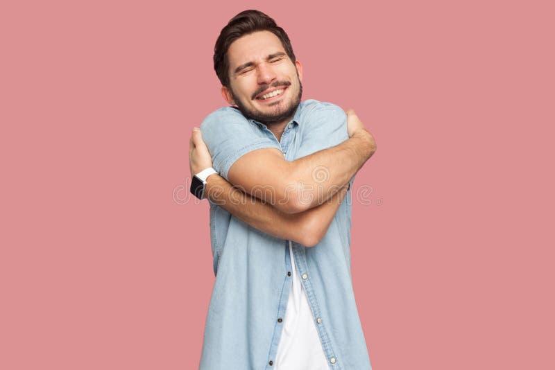 Portret van de gelukkige zelfgenoegzaamheids knappe gebaarde jonge mens in blauw toevallig overhemd die en bevinden koesteren zic stock foto