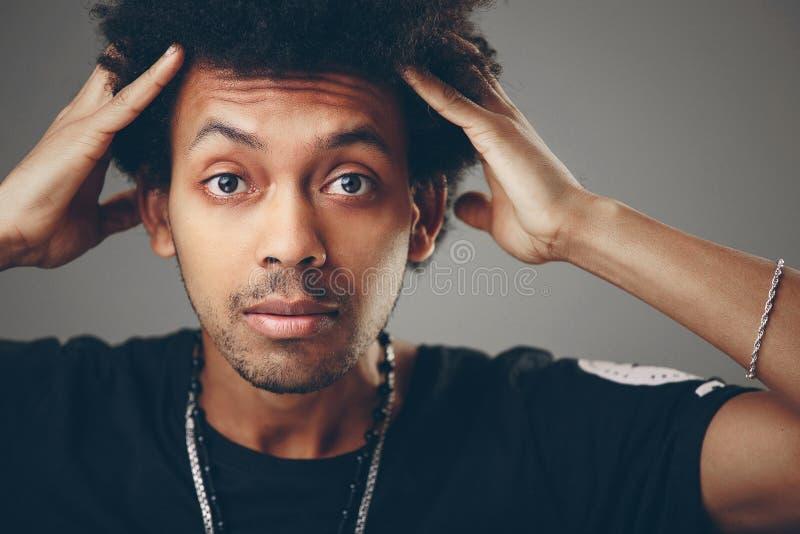 Portret van de geschokte jonge Afrikaanse Amerikaanse mens die camera bekijken stock foto's