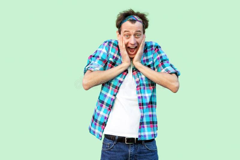 Portret van de geschokte jonge mens in toevallig blauw geruit overhemd en hoofdband die rakend zijn gezicht en bekijkend camera m stock afbeeldingen