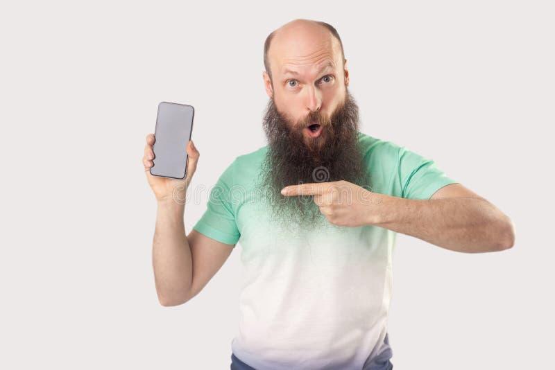 Portret van de geschokte midden oude kale gebaarde mens die zich met mobiele smartphone bevinden die op het lege scherm richten e royalty-vrije stock afbeelding