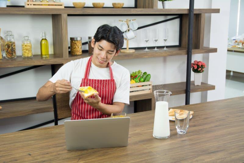 Portret van de gezonde volwassen mens in rode schort die en ontbijt thuis keuken glimlachen hebben stock afbeeldingen