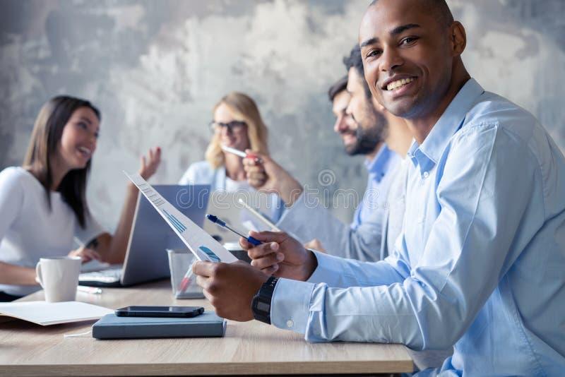 Portret van de glimlachende Afrikaanse Amerikaanse bedrijfsmens met stafmedewerkers die op achtergrond werken stock fotografie