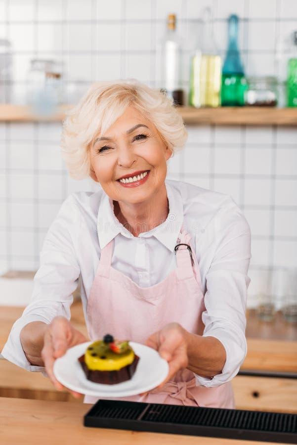portret van de glimlachende arbeider van de koffiewinkel in de plaat van de schortholding met dessert royalty-vrije stock afbeelding