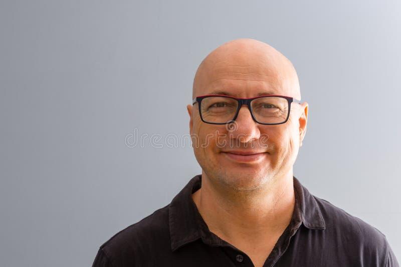 Portret van de glimlachende gewaagde volwassen mens stock afbeelding