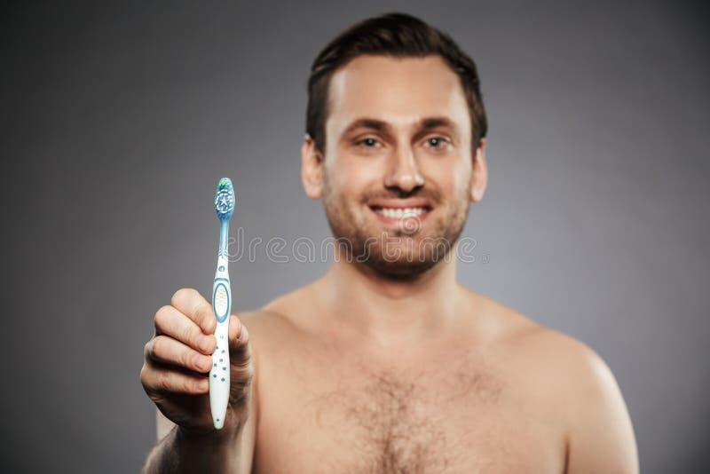Portret van de glimlachende halve naakte mens met varkenshaar die toothbru tonen stock afbeeldingen