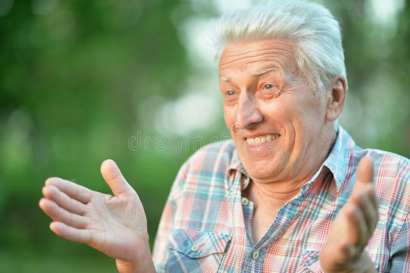 Portret van de glimlachende hogere mens in park stock fotografie