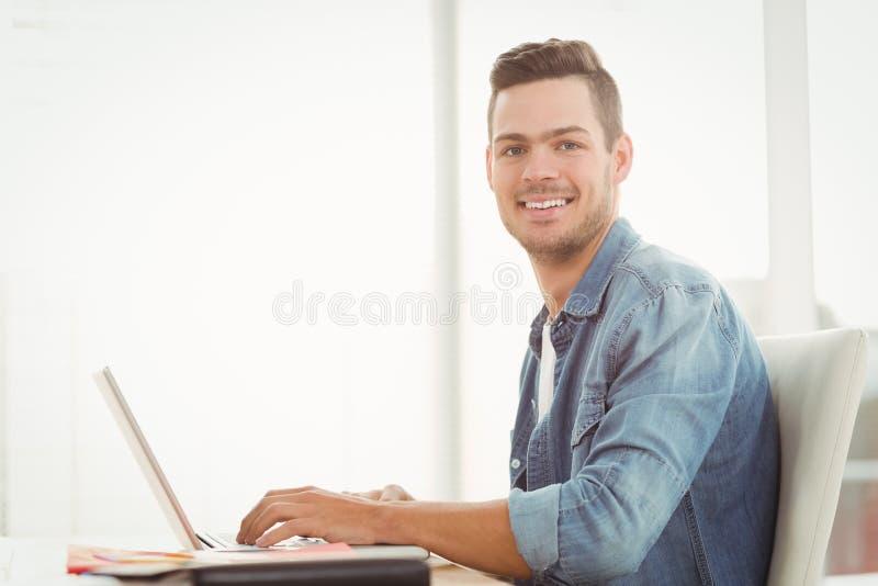Portret van de glimlachende jonge mens die aan laptop werkt stock foto