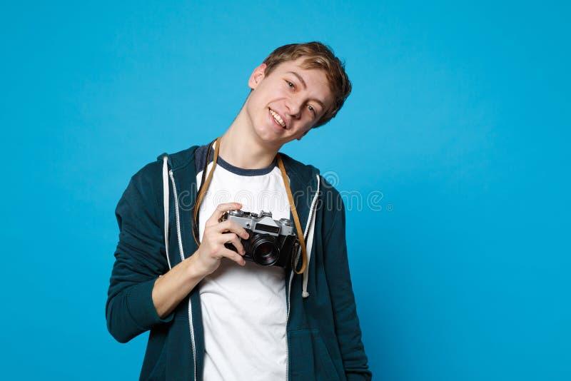 Portret van de glimlachende jonge mens in vrijetijdskleding die in camera houden van de handen retro uitstekende die foto op blau stock foto's