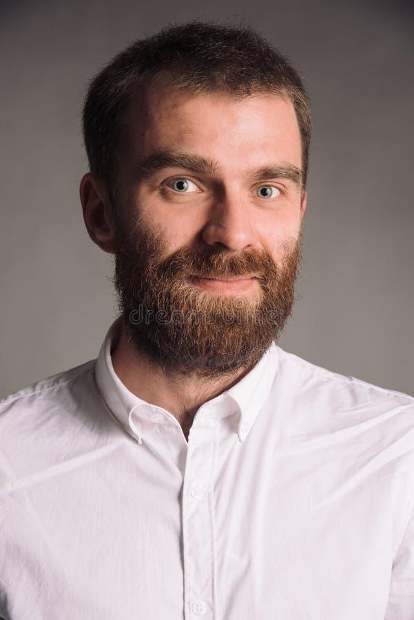 Portret van de glimlachende mens met baard in wit die overhemd bij het grijze studio stellen als achtergrond aan de camera wordt  stock afbeeldingen