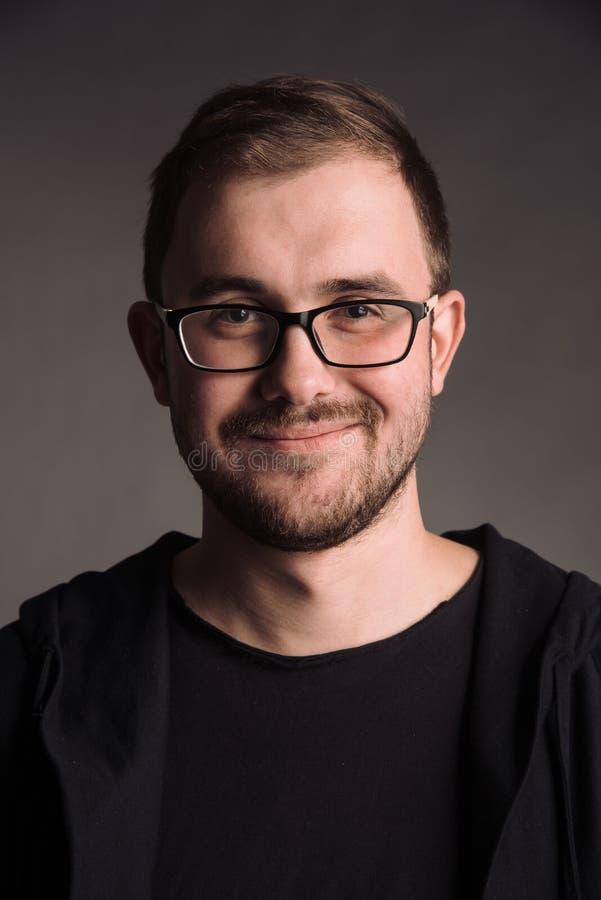 Portret van de glimlachende mens in zwarte t-shirt bij het grijze studio stellen als achtergrond aan de camera royalty-vrije stock afbeeldingen