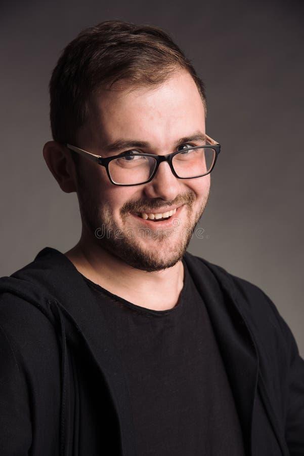 Portret van de glimlachende mens in zwarte t-shirt bij het grijze studio stellen als achtergrond aan de camera royalty-vrije stock foto's