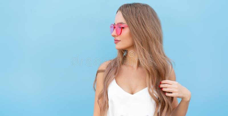 Portret van de glimlachende vrouw van de schoonheidsmanier met vliegend kapsel, in roze neonzonnebril op blauwe achtergrond toeva royalty-vrije stock afbeelding