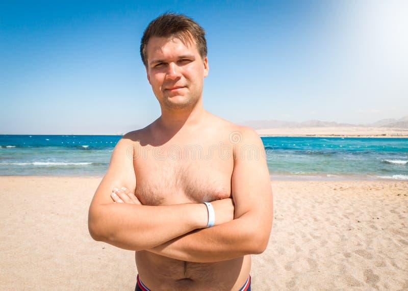 Portret van de glimlachende zwaarlijvige mens met het bovenmatige gewicht stellen op het overzeese strand en het kijken in camera royalty-vrije stock foto