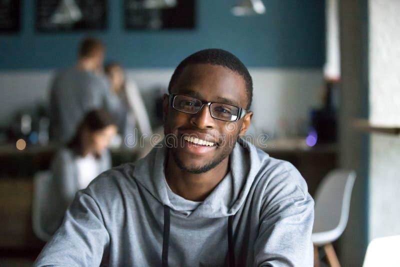 Portret van de glimlachende zwarte mens die camera in koffie bekijken royalty-vrije stock fotografie