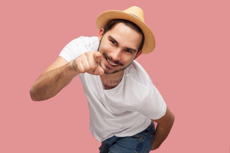 Portret van de grappige gebaarde jonge mens in wit overhemd met hoed die, en camera met toothy glimlach richten bekijken bevinden stock afbeeldingen