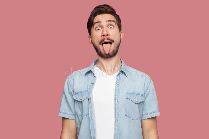 Portret van de grappige gekke knappe gebaarde jonge mens in blauw toevallig stijloverhemd die zich met grote ogen, tong bevinden  royalty-vrije stock foto
