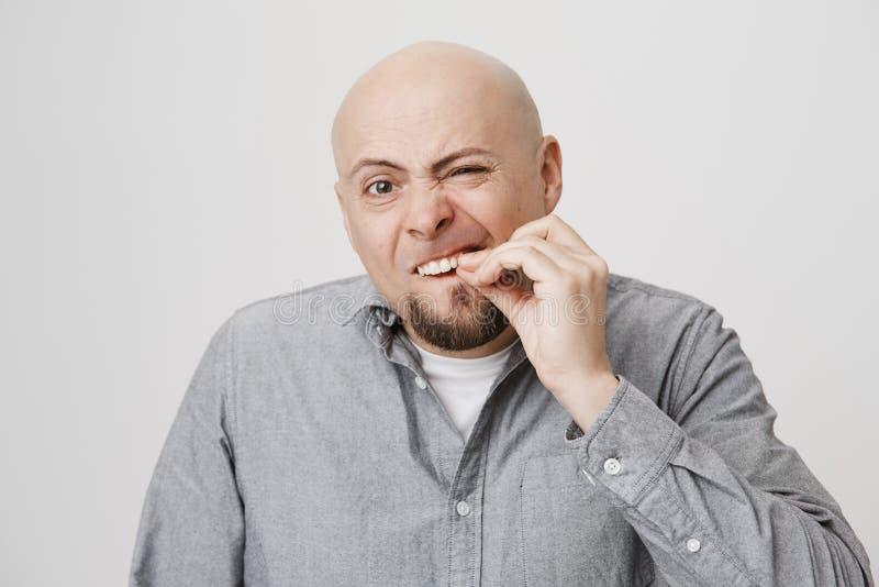 Portret van de grappige kale Kaukasische mens wat betreft zijn tand alsof willend het trekken uit, zich bevindt met geconcentreer stock fotografie