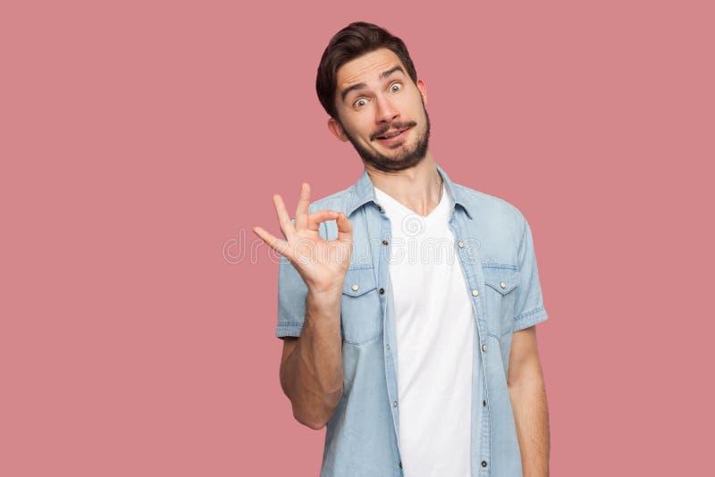 Portret van de grappige knappe gebaarde jonge mens in blauw toevallig stijloverhemd die zich met O.k. teken bevinden en camera me stock fotografie