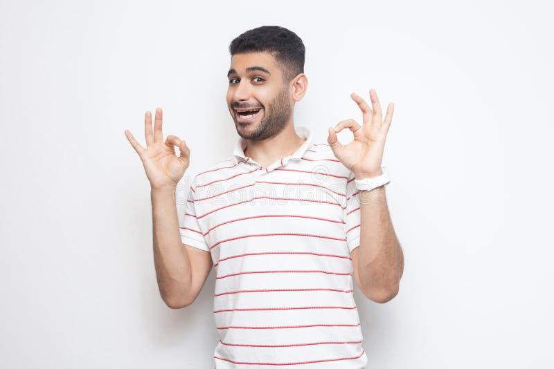 Portret van de grappige knappe gebaarde jonge mens in gestreepte t-shirt die zich met O.k. teken bevinden en camera met geluk bek royalty-vrije stock fotografie