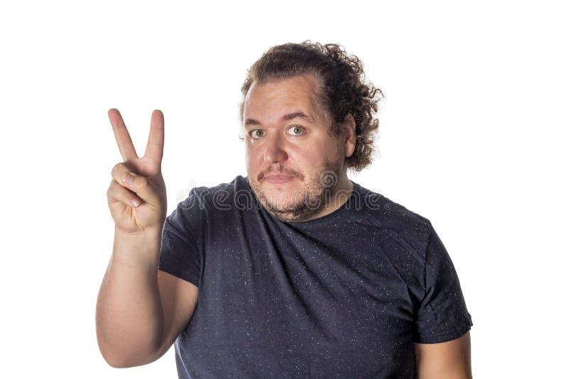 Portret van de grappige vette mens die vredes v-teken of overwinningsgebaar tonen stock fotografie