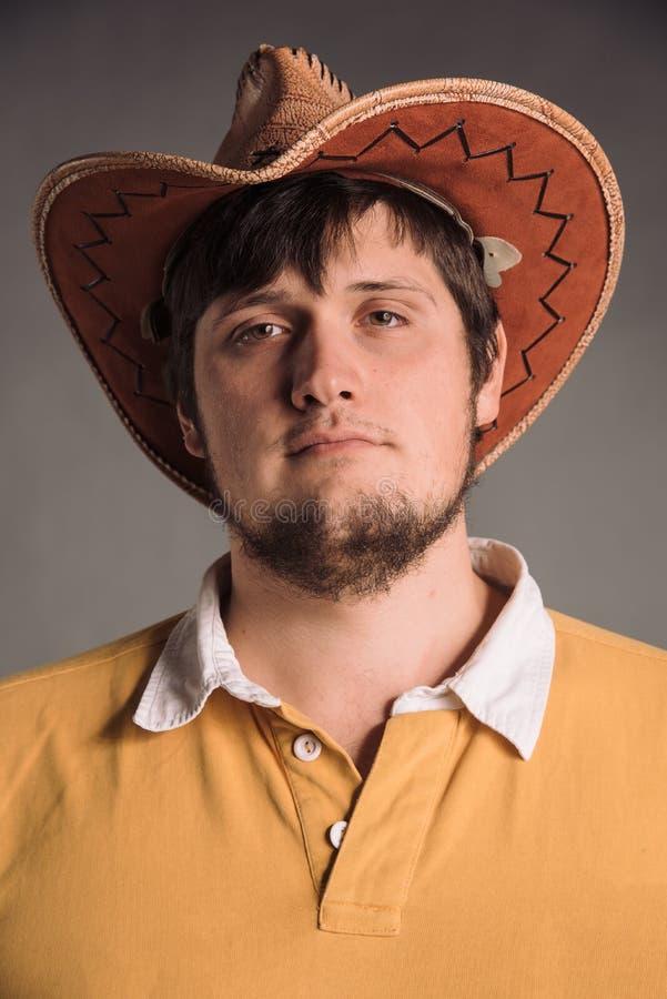 Portret van de grote mens in een cowboyhoed en een geel overhemd Jonge mens De studio schoot in de grijze muur Neutrale gelaatsui stock fotografie
