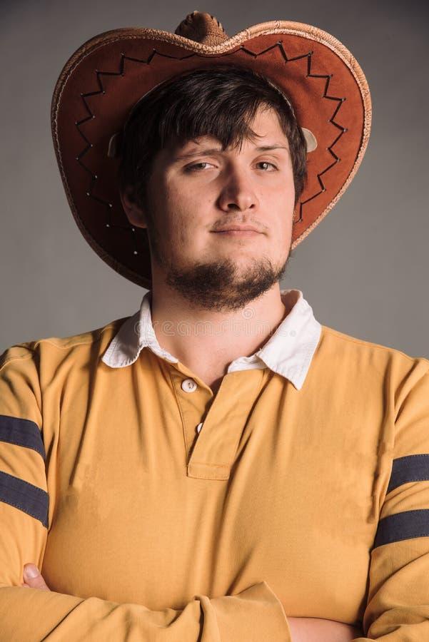 Portret van de grote mens in een cowboyhoed en een geel overhemd Sceptisch jonge mens De studio schoot in de grijze muur stock fotografie