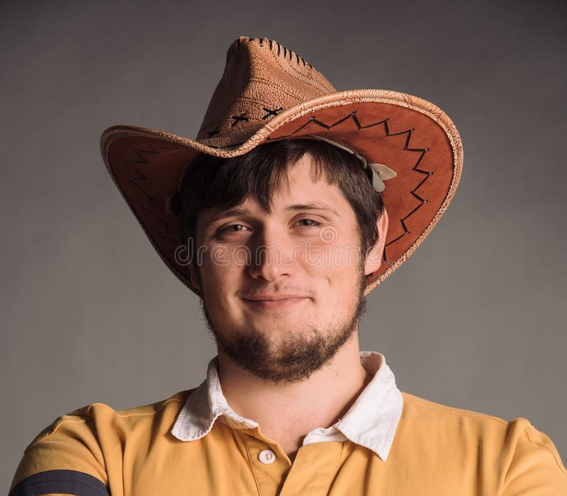 Portret van de grote mens in een cowboyhoed en een geel overhemd Smail Jonge mens De studio schoot in de grijze muur royalty-vrije stock foto's